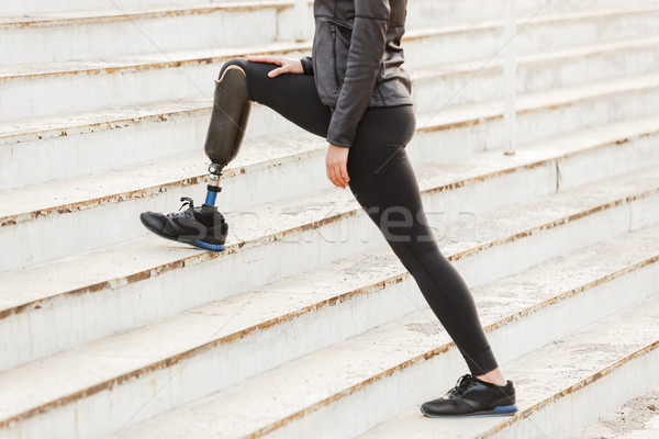 Cropped image of disabled running girl with prosthetic leg in sp Stock photo © deandrobot