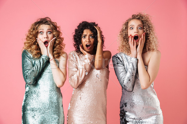 Three beautiful shocked women in shiny dresses Stock photo © deandrobot