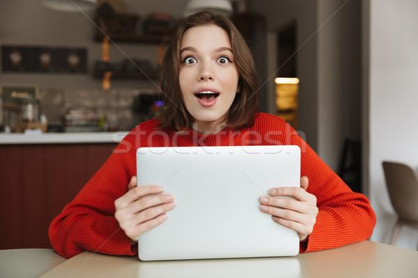 Fotó elragadtatott fiatal nő 20-as évek pulóver néz Stock fotó © deandrobot