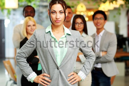 Smiling handsome businesswoman with team in office pointing finger at you Stock photo © deandrobot