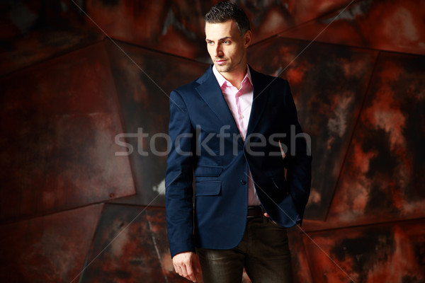 Cool fashion man standing and looking away over industrial background Stock photo © deandrobot