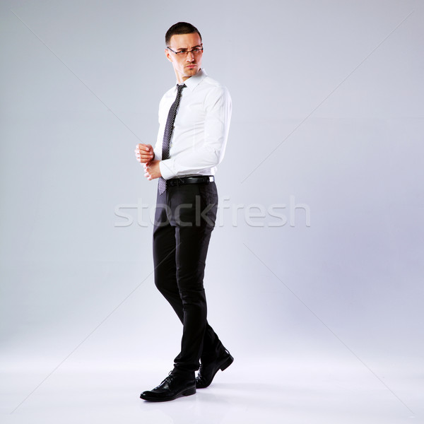 Full-length portrait of a pensive businessman on gray background Stock photo © deandrobot