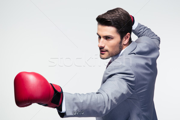 Businessman ready to fight with boxing gloves Stock photo © deandrobot
