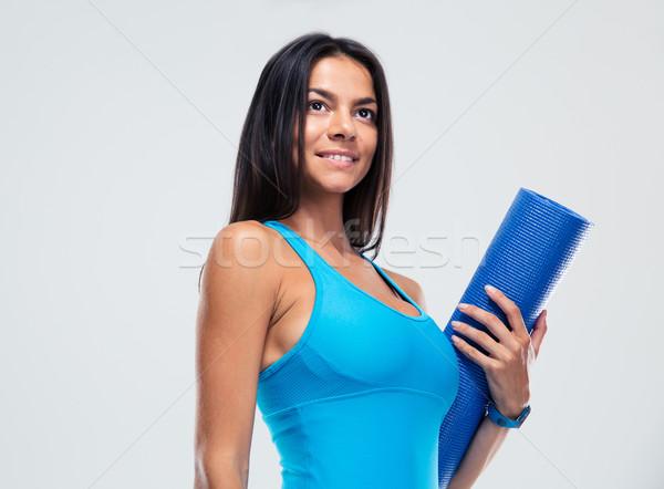 Smiling sports woman holding yoga mat  Stock photo © deandrobot