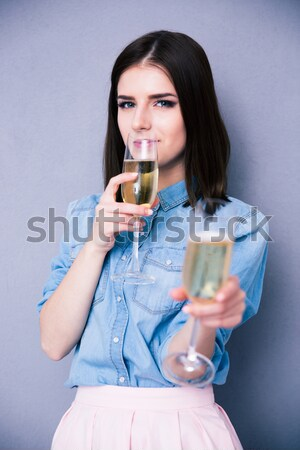 Woman holding glass of champagne and winking Stock photo © deandrobot