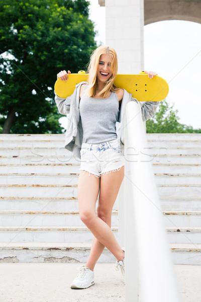 Fiatal lány áll gördeszka nevet kint park Stock fotó © deandrobot