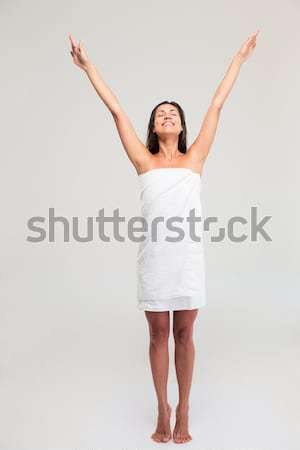 Woman in towel standing with raised hands up Stock photo © deandrobot