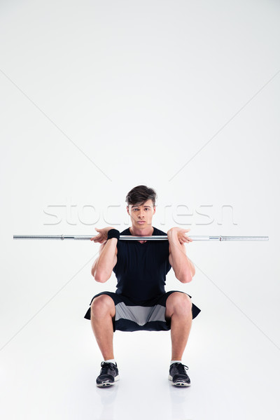 Athletic man doing squatting exercises with barbell Stock photo © deandrobot