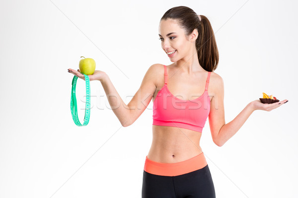 Charming happy young sportswoman choosing between healthy and unhealthy food Stock photo © deandrobot