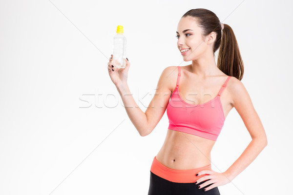 Souriant cute fitness fille regarder bouteille Photo stock © deandrobot
