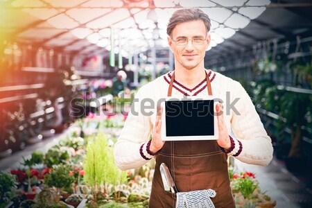 Férfi kertész ír jegyzettömb áll üvegház Stock fotó © deandrobot