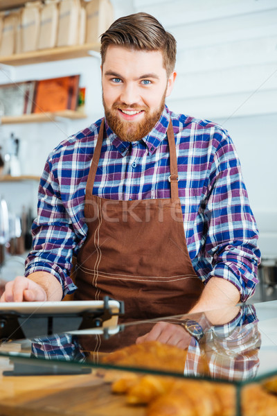 Potrait of happy bearded barista at work in coffe shop Stock photo © deandrobot