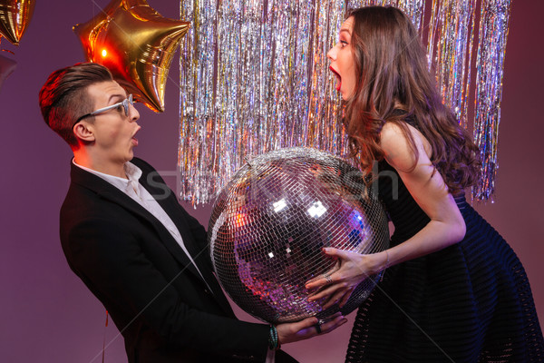 Attractive amazed young couple holding disco ball  Stock photo © deandrobot
