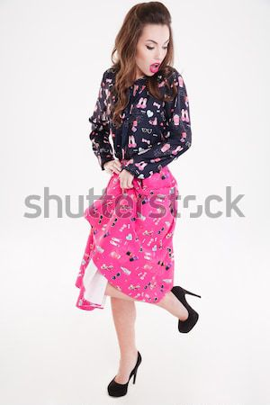 Playful cute young woman standing and looking back Stock photo © deandrobot