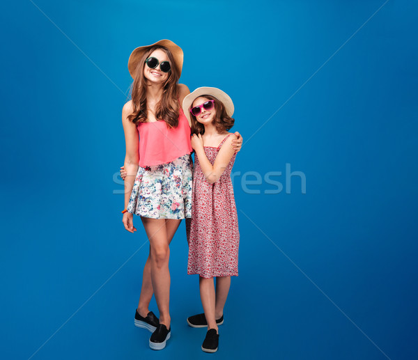 Two cheerful beautiful sisters standing together Stock photo © deandrobot