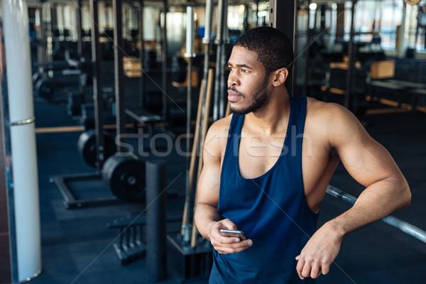 Afro american bodybuilder guy holding smartphone Stock photo © deandrobot