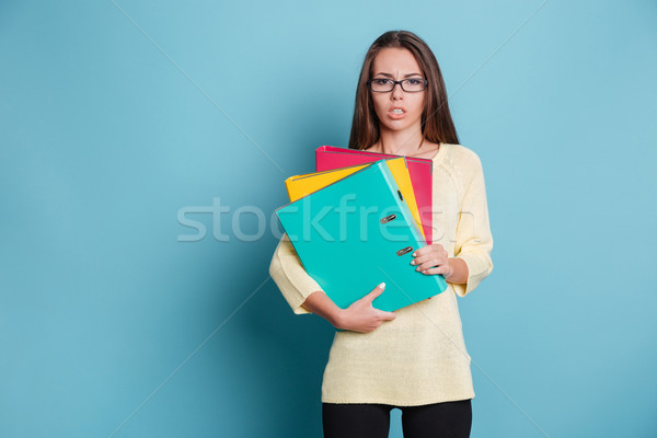 Concentrated young woman holding binders Stock photo © deandrobot