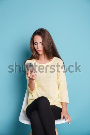 Pensive woman thinking about something and looking at the smartphone Stock photo © deandrobot