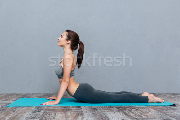 Young beautiful fitness girl doing yoga exercise Stock photo © deandrobot