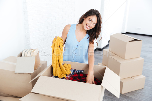 Portrait of a pretty young girl unpacking in new flat Stock photo © deandrobot