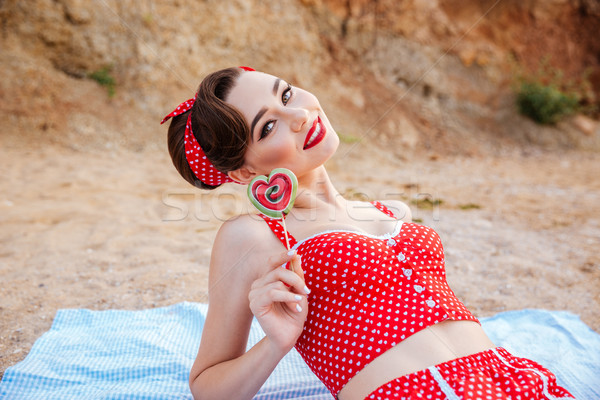 Happy young beautiful pin up girl holding heart shaped candy Stock photo © deandrobot