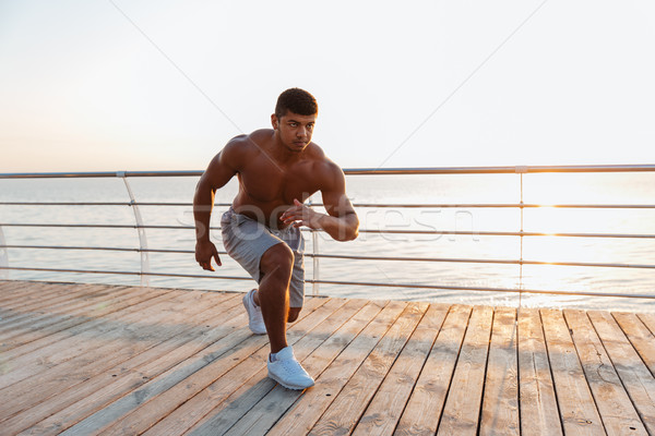 Shirtless african young sportsman working out on pier Stock photo © deandrobot