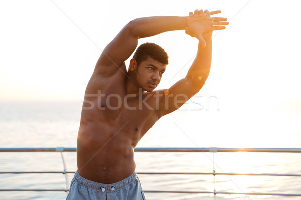 Handsome muscular african man athlete doing stretching exercises on pier Stock photo © deandrobot
