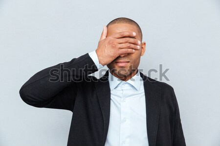 Portrait of a businessman covering eyes isolated on gray background Stock photo © deandrobot