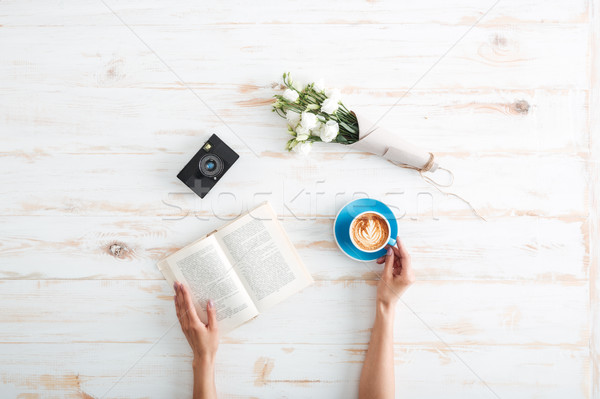 Female hands holding book and coffee cup on wooden desk Stock photo © deandrobot