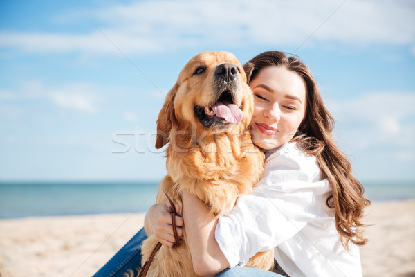 Tender smiling young woman hugging her dog on the beach Stock photo © deandrobot