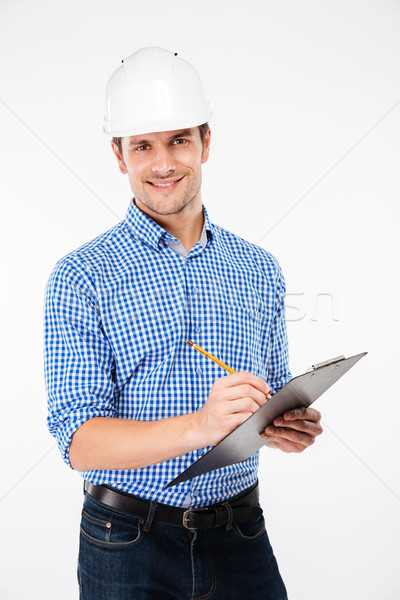 Smiling young man architect in building helmet writing on clipboard Stock photo © deandrobot