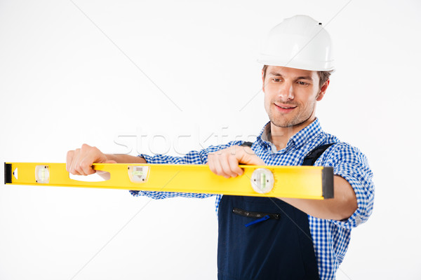 Portrait of a young worker in overalls using level tool Stock photo © deandrobot