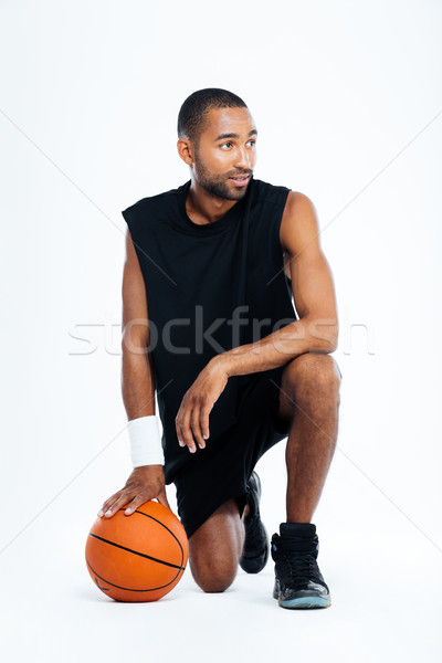Attractive young man basketball player standing on one knee Stock photo © deandrobot