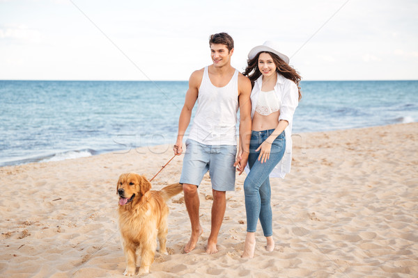 Romantic beautiful couple walking on the sea shore with dog Stock photo © deandrobot