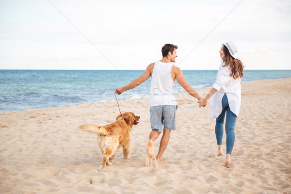 Happy joyful young couple running on beach with their dog Stock photo © deandrobot