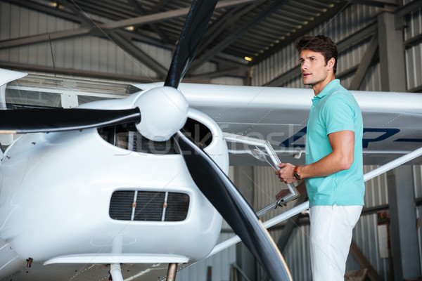 Man pilot standing near small private airplane Stock photo © deandrobot