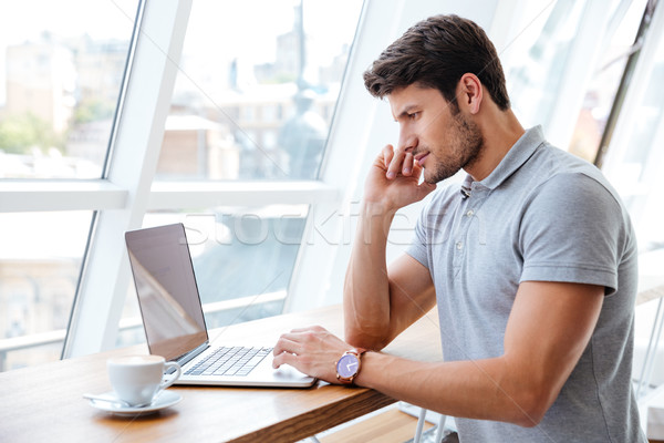 Handsome pensive man working with laptop while having coffee break Stock photo © deandrobot
