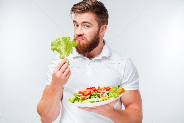 Upset bearded man smells lettuce and holding plate with salad Stock photo © deandrobot