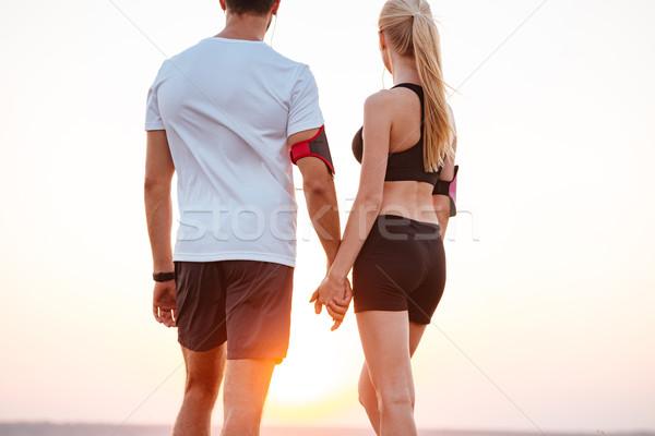 Couple permanent colline mains tenant regarder coucher du soleil Photo stock © deandrobot