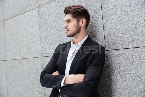 Grave jóvenes empresario pie los brazos cruzados perfil Foto stock © deandrobot