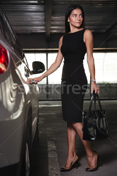 Happy young businesswoman opening the door of car on parking Stock photo © deandrobot