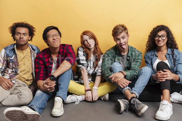 Comical playful young people sitting and making funny faces Stock photo © deandrobot