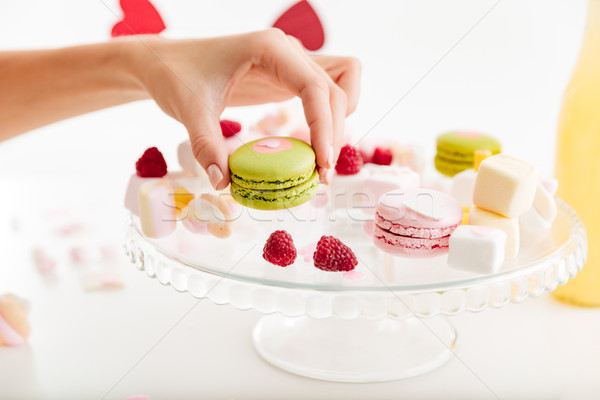 Hand taking green french macaroon from the plate with sweets Stock photo © deandrobot