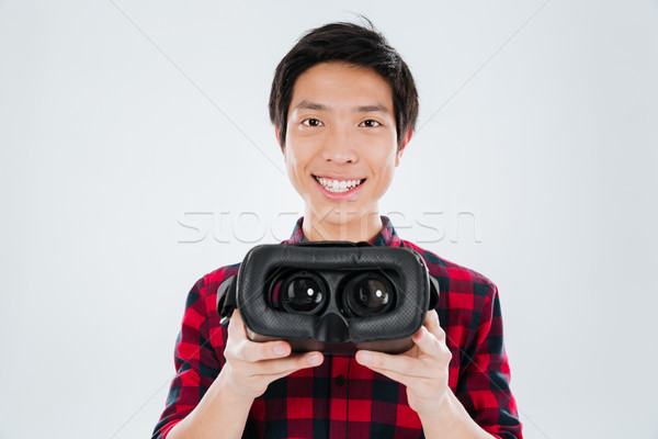 Asian man showing to camera virtual reality device Stock photo © deandrobot
