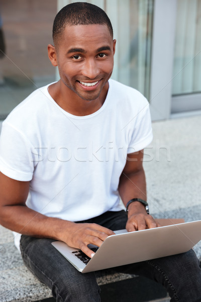 Cheerful african young man sitting and using laptop outdoors Stock photo © deandrobot