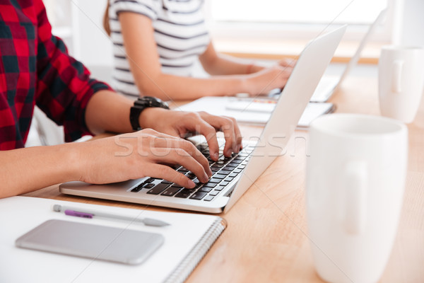 Cropped image of students typing on their laptops Stock photo © deandrobot