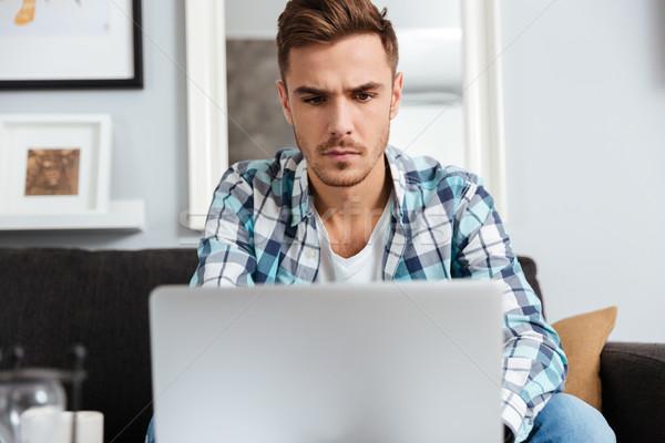 Concentrato setola uomo utilizzando il computer portatile computer immagine Foto d'archivio © deandrobot