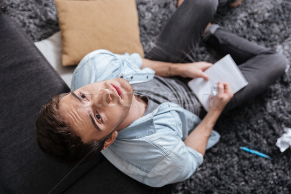 Man looking up and holding notepad while sitting on carpet Stock photo © deandrobot