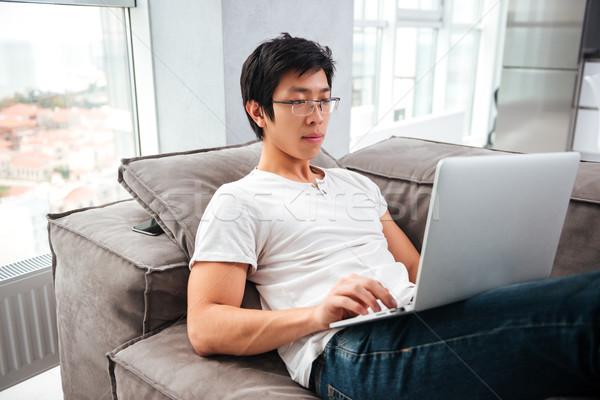 Widok z boku asian człowiek laptop sofa patrząc Zdjęcia stock © deandrobot