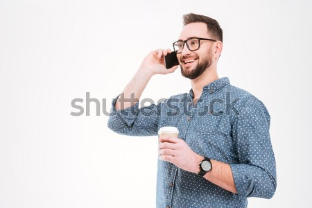 Man in eyeglasses standing with arms folded while being photographed Stock photo © deandrobot